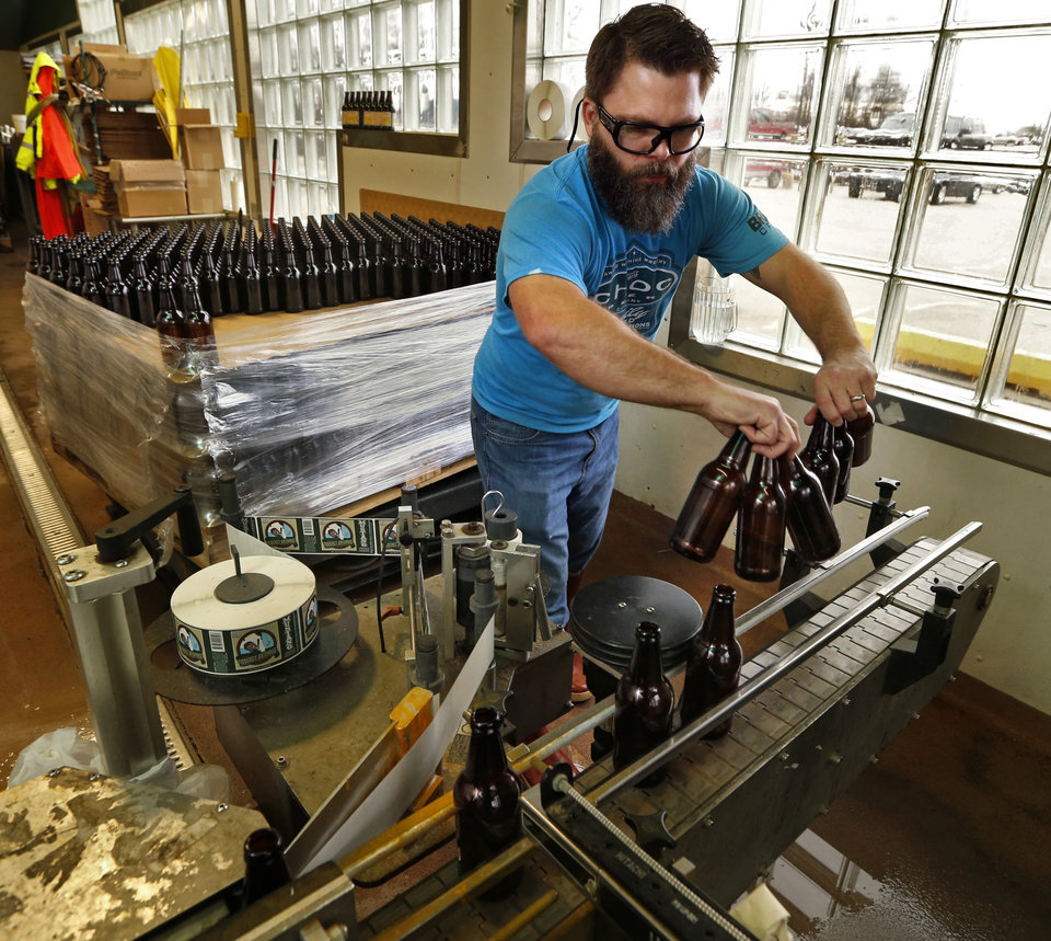 Photo -  Haven Wilkinson loads bottles on a labeler for Choc Beer at Krebs Brewing Co. in Krebs. [Photo by Steve Sisney, The Oklahoman Archives]