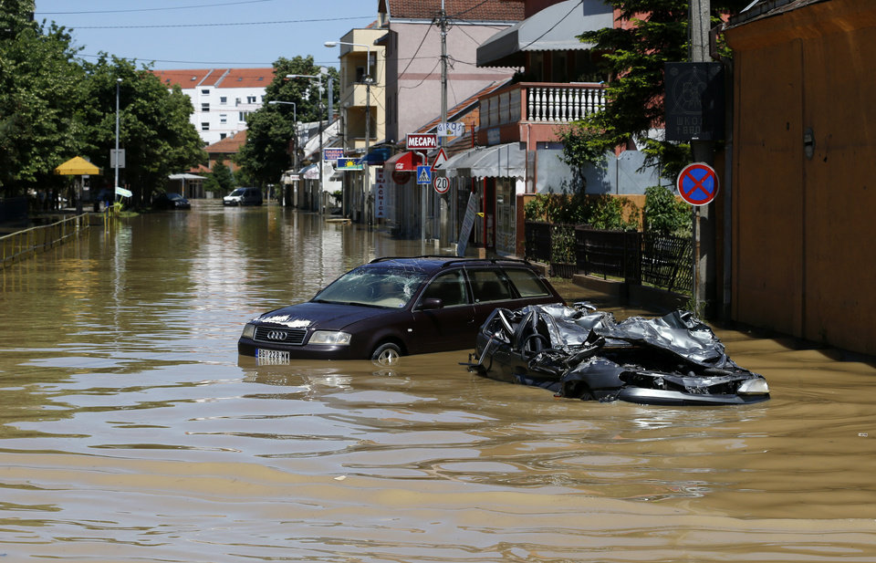 Photo - A severely damaged car  stands in a flooded street in Obrenovac, some 30 kilometers (18 miles) southwest of Belgrade, Serbia, Monday, May 19, 2014. Belgrade braced for a river surge Monday that threatened to inundate Serbia's main power plant and cause major power cuts in the crisis-stricken country as the Balkans struggle with the consequences of the worst flooding in southeastern Europe in more than a century. At least 35 people have died in Serbia and Bosnia in the five days of flooding caused by unprecedented torrential rain, laying waste to entire towns and villages and sending tens of thousands of people out of their homes, authorities said. (AP Photo/Darko Vojinovic)