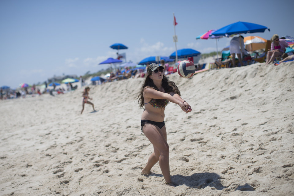 Photo - In this photo taken on Friday, July 11, 2014, a beachgoer strikes a volleyball in Southampton, N.Y. Studies show the gap separating the rich from the working poor has been ever-widening in recent years and few places provide that evidence as starkly as Long Island's Hamptons. (AP Photo/John Minchillo)