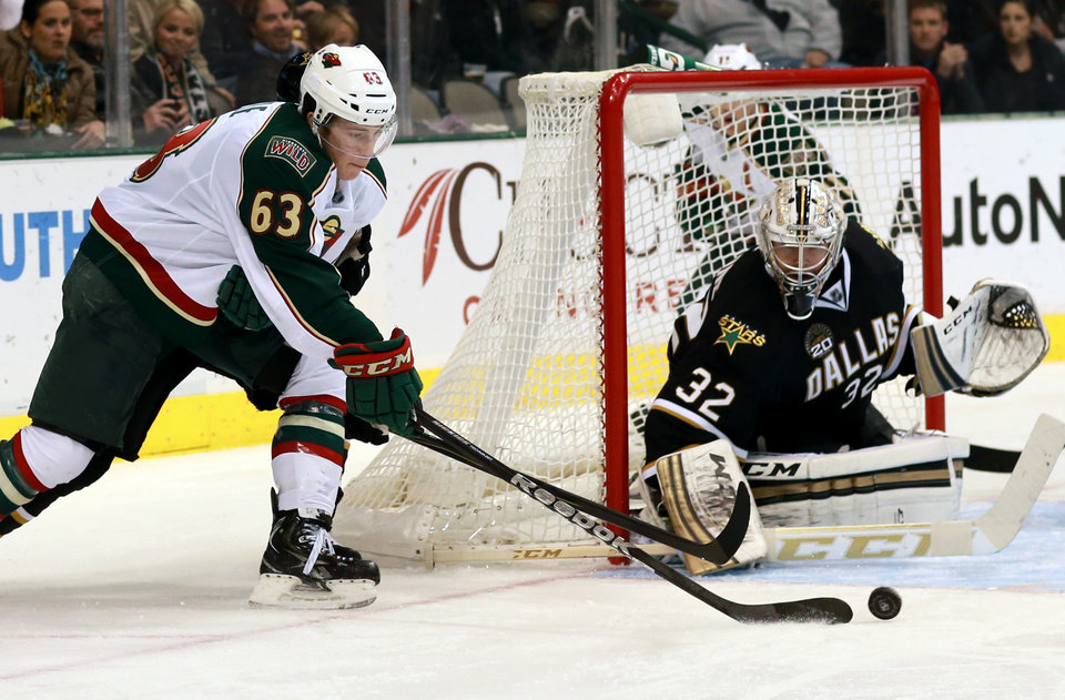 Photo - Minnesota Wild right wing Charlie Coyle (63) sets up a shot on Dallas Stars goalie Kari Lehtonen (32) during the second period of an NHL hockey game Monday, March 25, 2013 in Dallas. (AP Photo/ Michael Mulvey)
