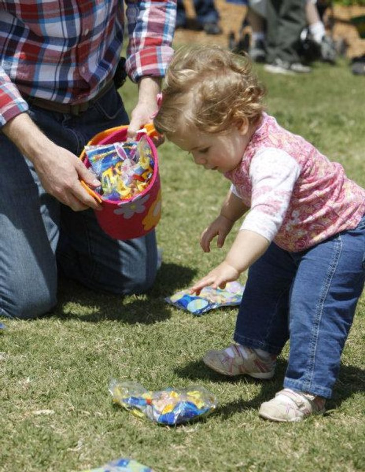 Photo - Sara Powitzky, 14 months, picks up treats during an Easter egg hunt and carnival Saturday at Plunkett Park at the University of Central Oklahoma in Edmond. Photo by Paul Hellstern, The Oklahoman  PAUL HELLSTERN