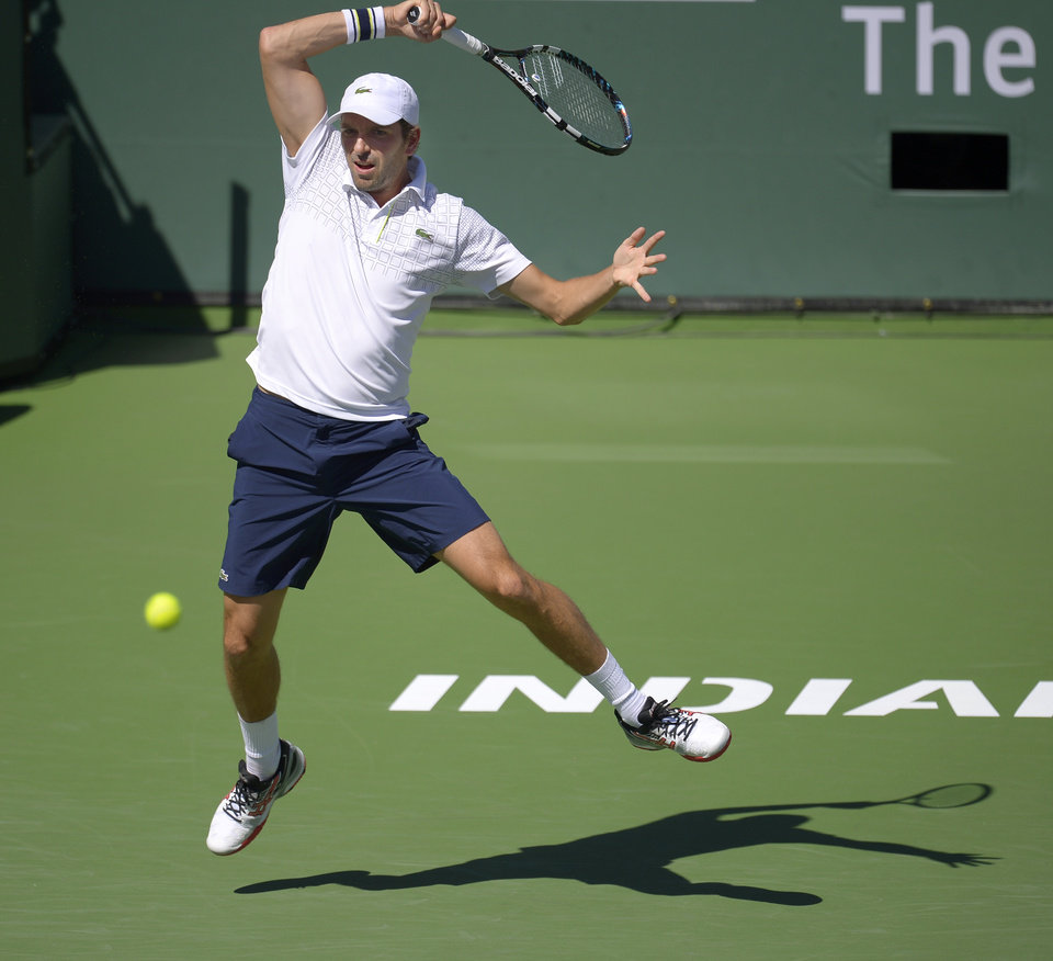 Photo - Julien Benneteau, of France, volleys with Novak Djokovic, of Serbia, in their quarterfinal match at the BNP Paribas Open tennis tournament, Friday, March 14, 2014, in Indian Wells, Calif. (AP Photo/Mark J. Terrill)