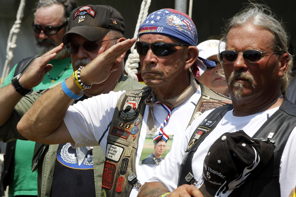 Photo -   Members of Rolling Thunder salute during the presentation of colors during the annual Rolling Thunder rally on the National Mall ahead of Memorial Day in Washington, Sunday, May 27, 2012. (AP Photo/Charles Dharapak)