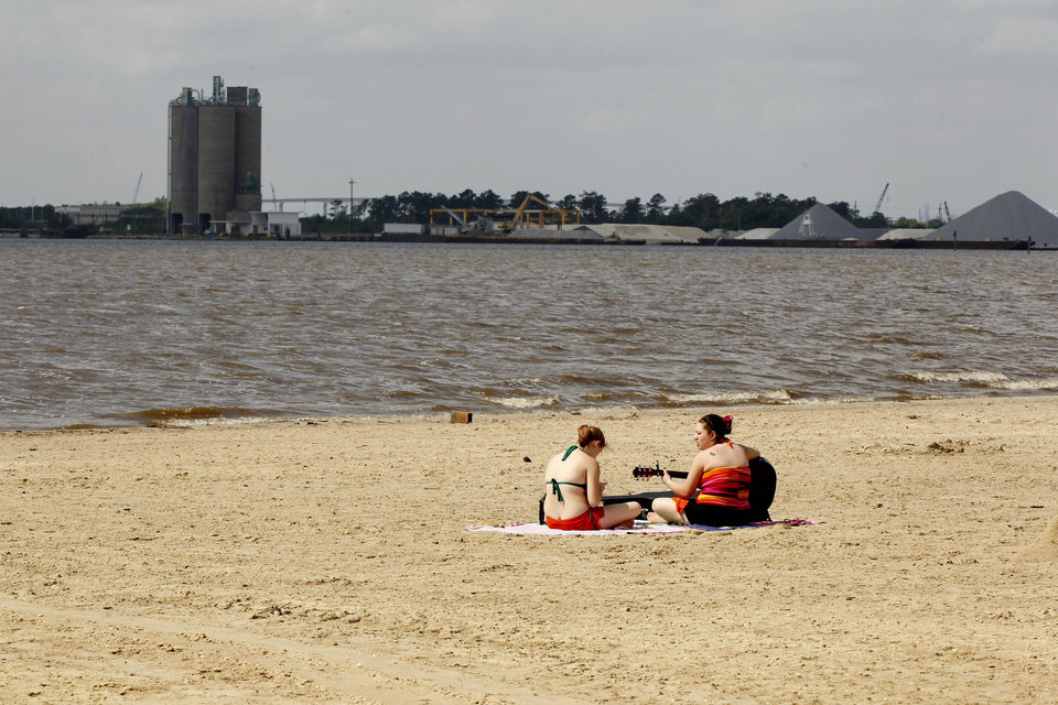 "This photo taken April 13, 2012, shows people sunning themselves on a beach on Lake Charles, La., opposite a cement terminal on the far side of the lake near the site of the old Olin-Matheison Plant. The view from the same vantage point was photographed for ""Documerica"" program, 1972-1977, instituted by the then new Environmental Protection Agency, to document subjects of environmental concern. (AP Photo/Gerald Herbert)"