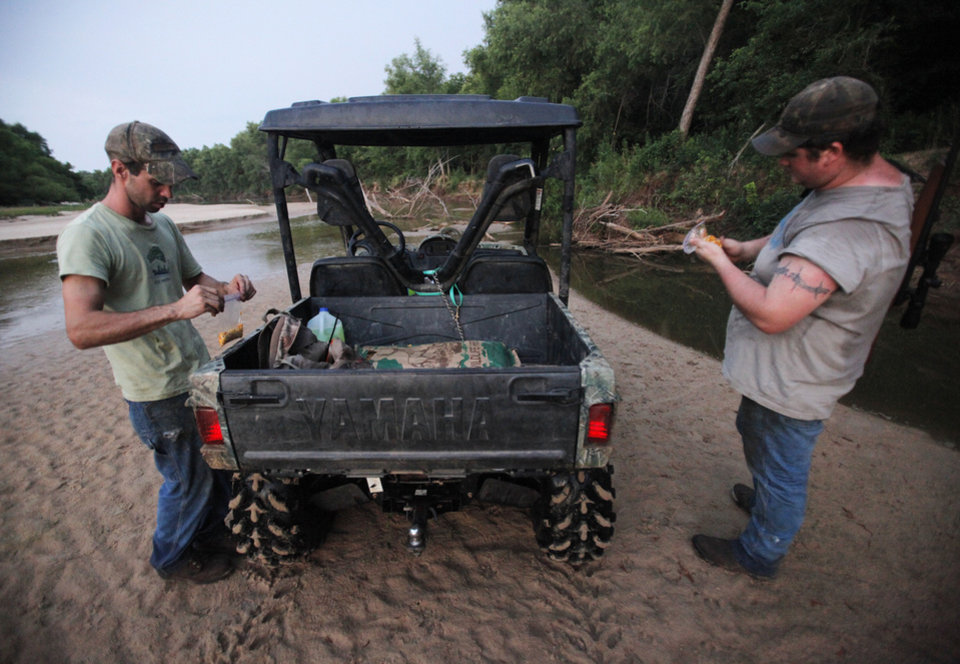 Johnny Heskett and Josh Kinsey prepare hog traps during a hunting trip near Indianola, Okla., Friday, July 6, 2012.  Photo by Garett Fisbeck, The Oklahoman