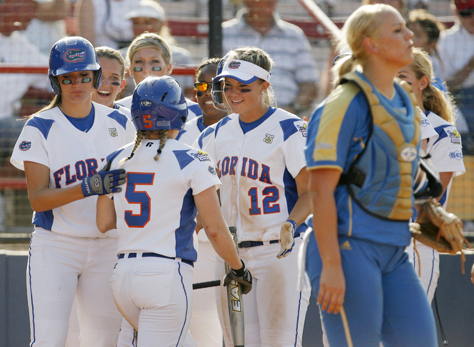 Florida's Kim Waleszonia (5) is met by her teammates behind UCLA catcher Jennifer Schroeder (27) after Waleszonia scored in the first inning during the softball game in the Women's College World Series between UCLA and Florida at ASA Hall of Fame Stadium in Oklahoma City, Saturday, May 31, 2008. BY NATE BILLINGS, THE OKLAHOMAN