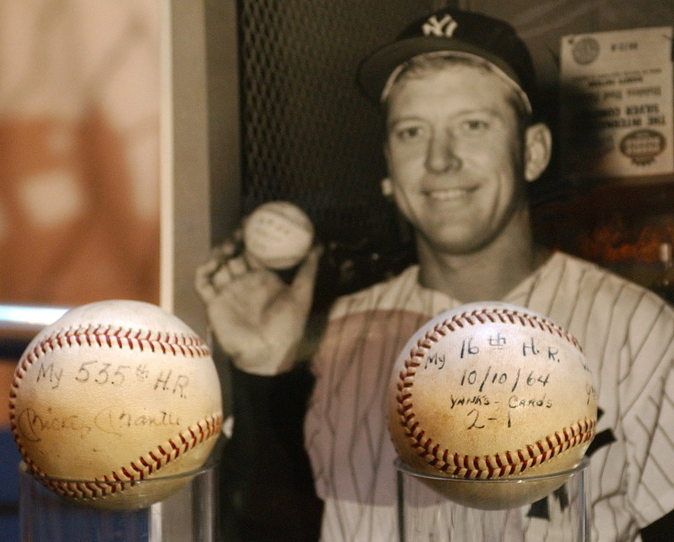 Photo - FORMER OKLAHOMAN / MAJOR LEAGUE BASEBALL: **FiLE** Two baseballs and a photo of Mickey Mantle, holding the ball shown at right, are displayed at a press conference in New York in this Nov. 13, 2003, file photo. Three hundred pieces of Mickey Mantle memorabilia were auctioned by Guernsey's auction house at New York City's Madison Square Garden on Monday, Dec. 8, 2003. (AP Photo/Ed Bailey, File)