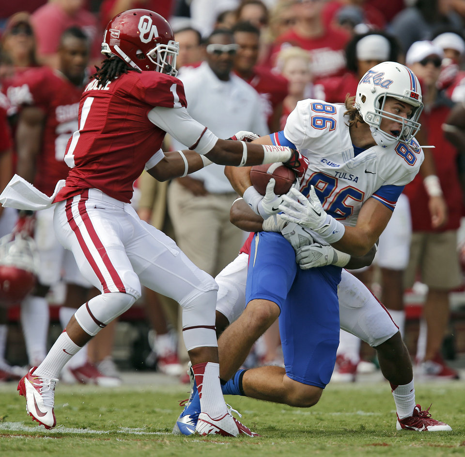 Photo - Oklahoma's L.J. Moore (1) tries to strip the ball from Tulsa 's Zach Epps (86) during the college football game between the University of Oklahoma Sooners (OU) and the University of Tulsa Hurricanes (TU) at the Gaylord-Family Oklahoma Memorial Stadium on Saturday, Sept. 14, 2013 in Norman, Okla.  Photo by Chris Landsberger, The Oklahoman
