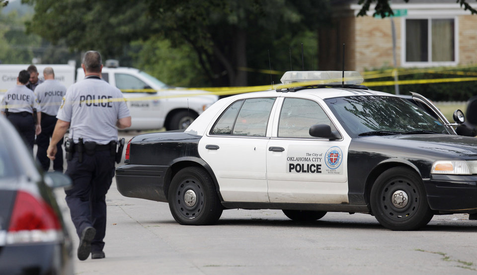 Photo - An Oklahoma City police investigator walks past an Oklahoma City police car riddled with bullet holes sitting on Miller Avenue just south of NW 39 Street Monday, August 30, 2010. A female Oklahoma City police officer was shot in the car. Photo by Paul B. Southerland, The Oklahoman