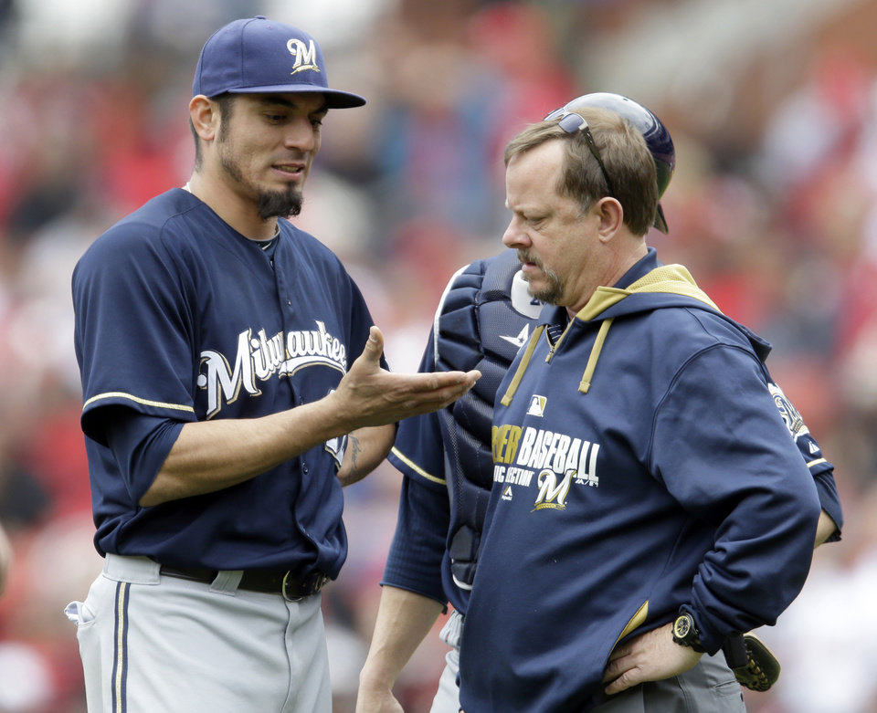 Photo - Milwaukee Brewers starting pitcher Matt Garza, left, shows his hand to trainer Dan Wright during the fourth inning of a baseball game against the St. Louis Cardinals Wednesday, April 30, 2014, in St. Louis. Garza left the game due to an injury. (AP Photo/Jeff Roberson)