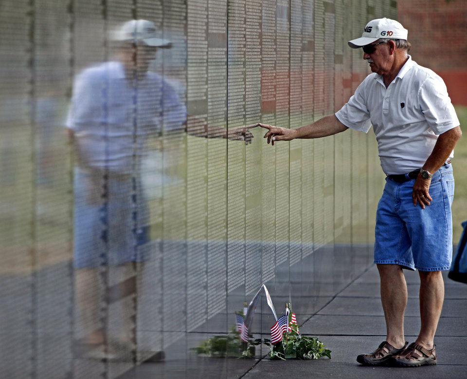 Army veteran Carl Higgins of Norman searches for a name of a friend on the Dignity Memorial Vietnam Wall before an opening ceremony at Reaves Park in Norman, Okla., Wednesday, June 30, 2010.  Photo by Bryan Terry, he Oklahoman