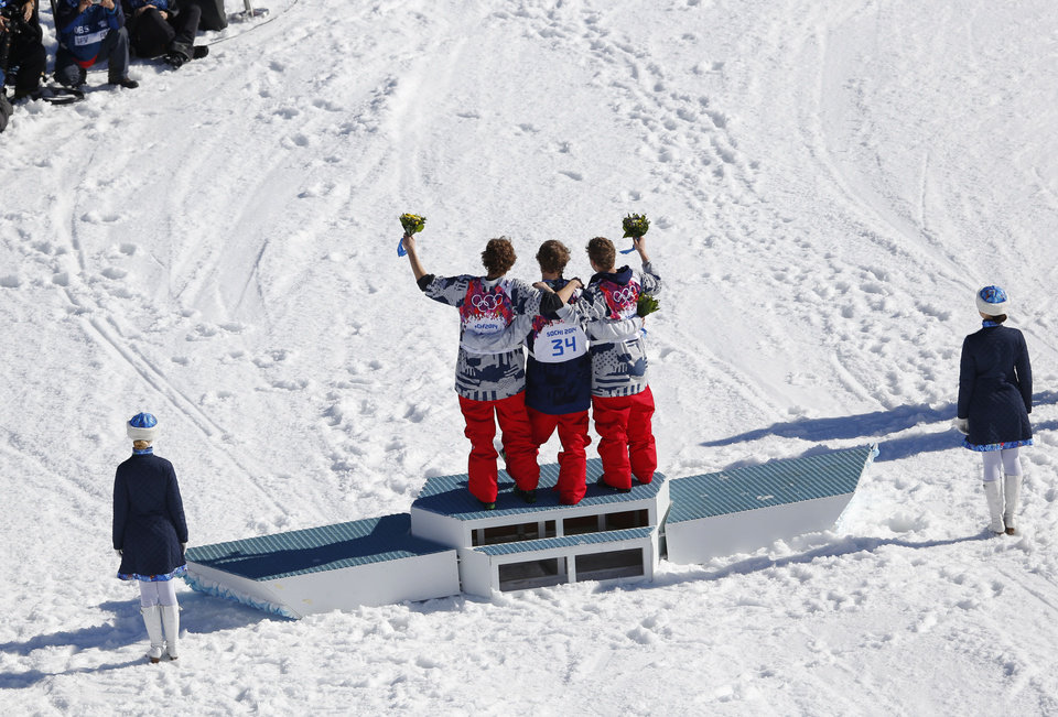 Photo - Men's ski slopestyle gold medal winner Joss Christensen of the United States, center, celebrates on the podium with his teammates Gus Kenworthy, right, silver, and Nicholas Goepper, bronze, left, during a flower ceremony at the Rosa Khutor Extreme Park, at the 2014 Winter Olympics, Thursday, Feb. 13, 2014, in Krasnaya Polyana, Russia.  (AP Photo/Sergei Grits)