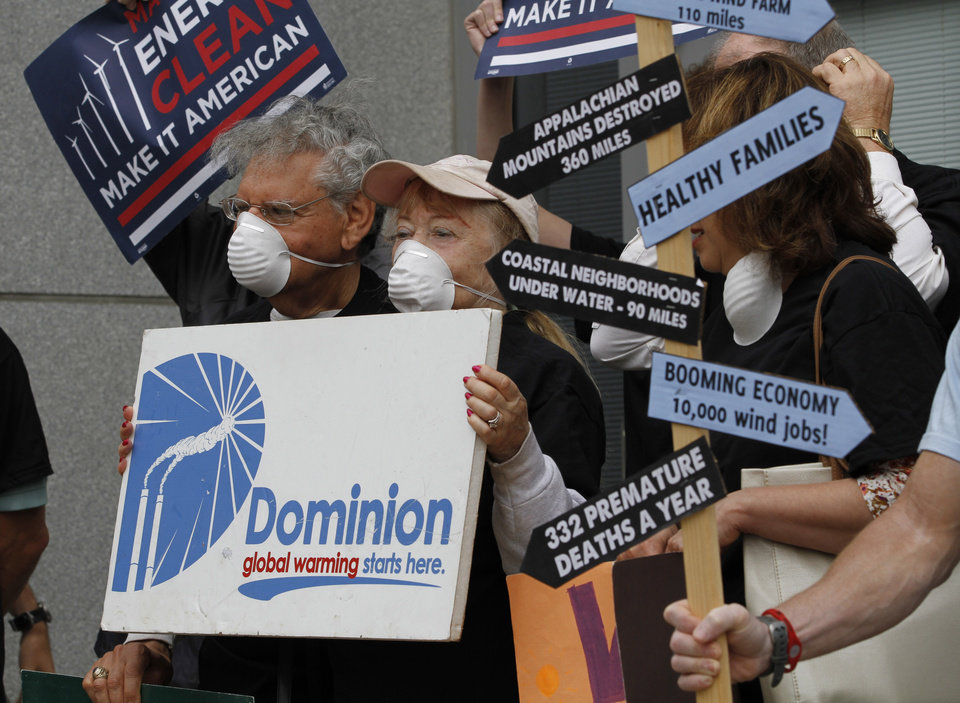 Photo -   Environmental activist carry signs and wear dust masks as they protest outside the State Corporations Commission in Richmond, Va., Tuesday, May 8, 2012. Dominion Virginia power presented it's long term energy plans to state regulators. (AP Photo/Steve Helber)