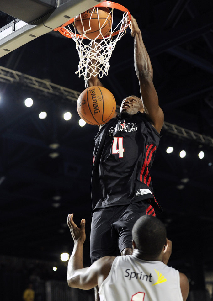 Photo - Olympic gold medalist Usain Bolt (4) dunks over comedian Kevin Hart in the first quarter of the NBA All-Stars celebrity basketball game on Friday, Feb. 15, 2013, in Houston. (AP Photo/Pat Sullivan)