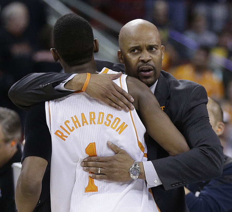Photo - Tennessee head coach Cuonzo Martin embraces Tennessee guard Josh Richardson after the second half of an NCAA college basketball third-round tournament game against Mercer, Sunday, March 23, 2014, in Raleigh. Tennessee Won 83-63. (AP Photo/Chuck Burton)