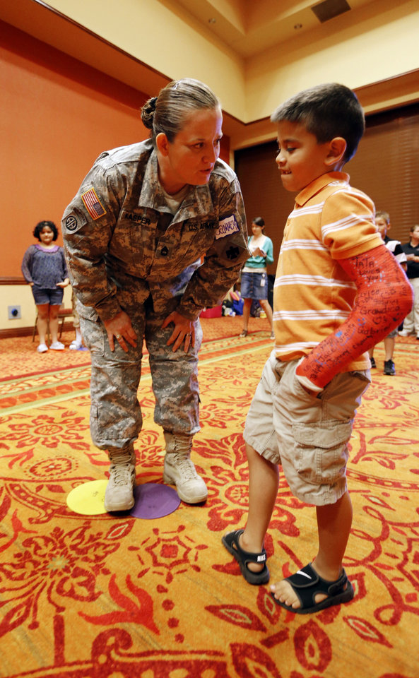 Photo - Sgt. 1st Class Cammey Kasper works with children in a get-to-know-you game in the children's activity section of the Yellow Ribbon Program for the families of deploying troops June 1 in Norman. Though the Solis' five children did not attend, the couple collected materials and handouts distributed at the event for them to use at home. Photo by Steve Sisney, The Oklahoman  STEVE SISNEY - THE OKLAHOMAN