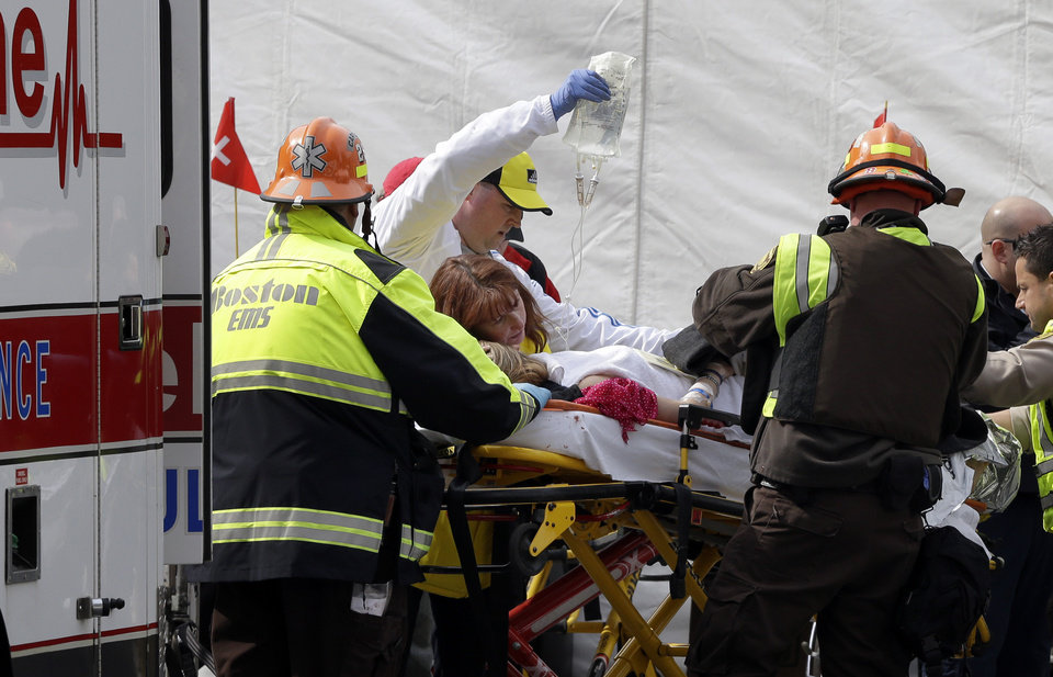 An injured person is loaded into an ambulance in the aftermath of two blasts which exploded near the finish line of the Boston Marathon in Boston Monday, April 15, 2013. Two bombs exploded near the finish line of the Boston Marathon on Monday, killing two people, injuring 23 others and sending authorities rushing to aid wounded spectators. A senior U.S. intelligence official said two other explosive devices were found nearby.  (AP Photo/Elise Amendola)  ORG XMIT: MAEA126