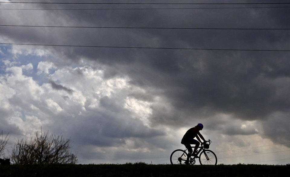 Photo - Dark clouds build Tuesday as a cyclist rides around Lake Overholser in Oklahoma City.  Photo by Chris Landsberger, The Oklahoman
