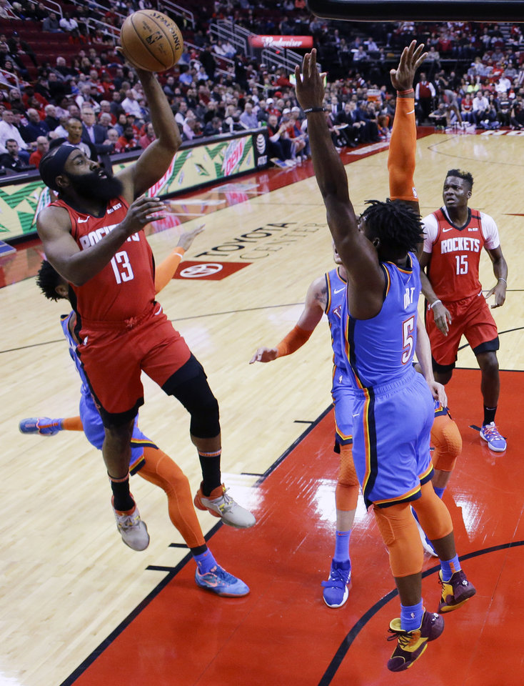 Photo - Houston Rockets guard James Harden (13) shoots as Oklahoma City Thunder guard Luguentz Dort defends during the first half of an NBA basketball game, Monday, Jan. 20, 2020, in Houston. (AP Photo/Eric Christian Smith)