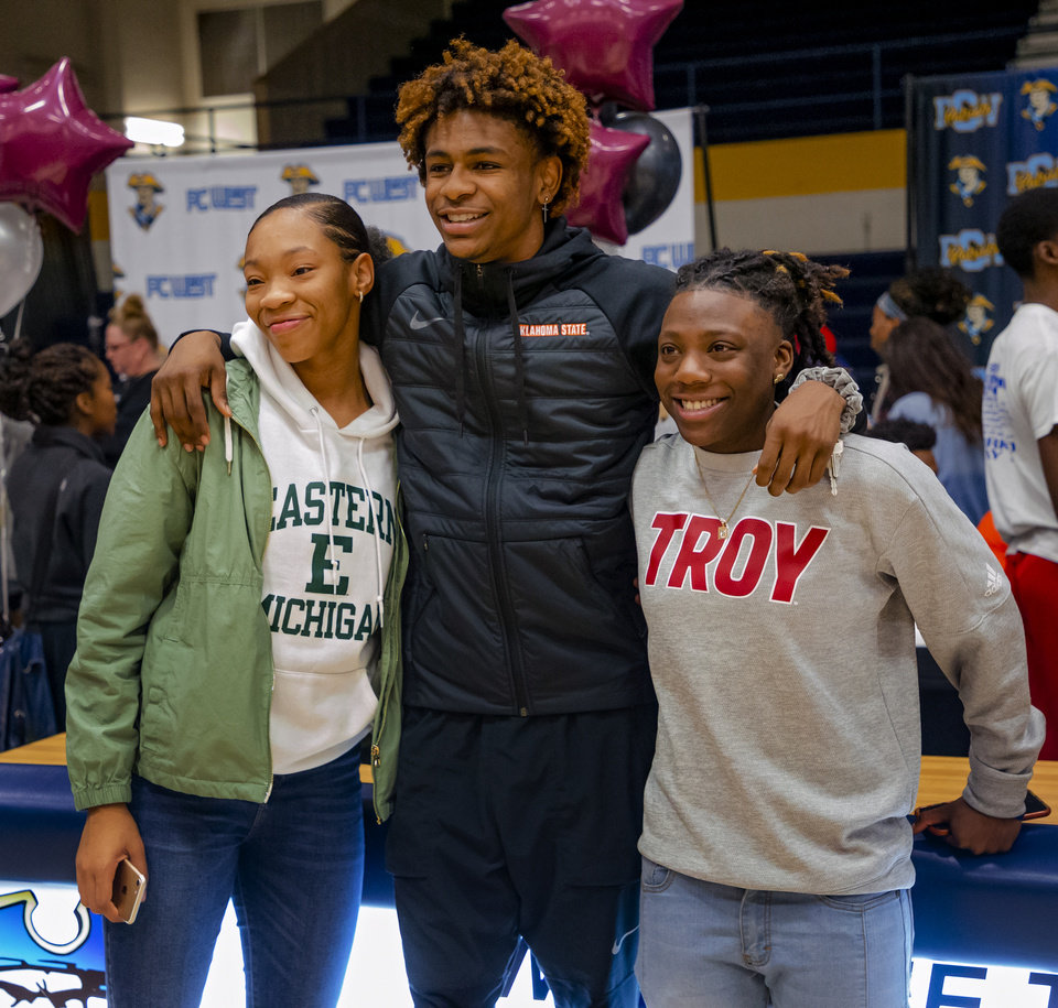 Photo - Putnam City West basketball players Rondel Walker, center poses for a photo with Zaniya Nelson, left, and Sharonica Hartsfield during an early signing day ceremony at Putnam City West High School in Oklahoma City, Okla. on Wednesday, Nov. 13, 2019.  Walker signed to play for Oklahoma State University (OSU), Nelson signed to play for Eastern Michigan and Hartsfield signed to play for Troy University.   [Chris Landsberger/The Oklahoman]
