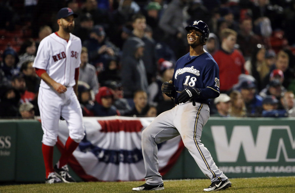 Photo - Milwaukee Brewers' Khris Davis (18) smiles after crossing home with the go-ahead run against Boston Red Sox relief pitcher Burke Badenhop, left, during the eleventh inning of a baseball game at Fenway Park in Boston, Saturday, April 5, 2014. (AP Photo/Winslow Townson)