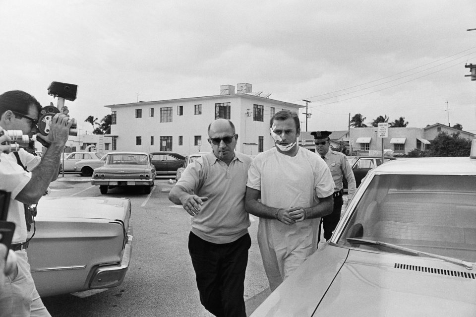 "FILE - In this Jan. 28, 1968 file photo, Jack ""Murph the Surf"" is escored to the Miami Beach Police Station by detectives in Miami Beach, Fla., after he was arrested with three other men for armed robbery. Murphy, the famed jewel thief and surfer known as ""Murph the Surf,"" has spent the last quarter-century going into prisons and telling inmates that they could still turn their lives around.  Now 75, he asked the state of Florida to restore his civil rights despite the fact he spent nearly 20 years in prison for murder. The answer: No. (AP Photo, File)"
