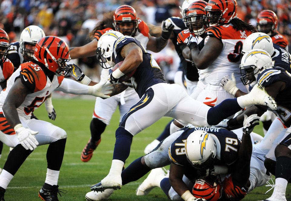 San Diego Chargers running back Ryan Mathews, center, leaps over two players against the Cincinnati Bengals defense during the second half of an NFL football game, Sunday, Dec. 2, 2012, in San Diego. (AP Photo/Denis Poroy)