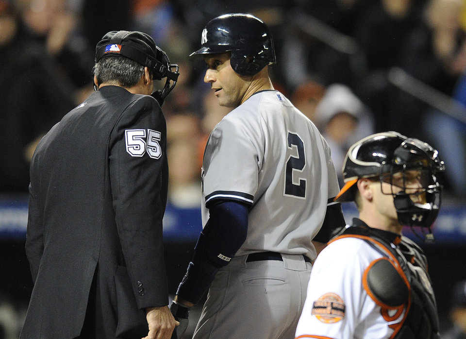 New York Yankees' Derek Jeter, center, speaks with umpire Angel Hernandez after striking out in the second inning of Game 2 of the American League division baseball series against the Baltimore Orioles on Monday, Oct. 8, 2012, in Baltimore. Also pictured is Orioles catcher Matt Wieters, at bottom right. (AP Photo/Nick Wass)
