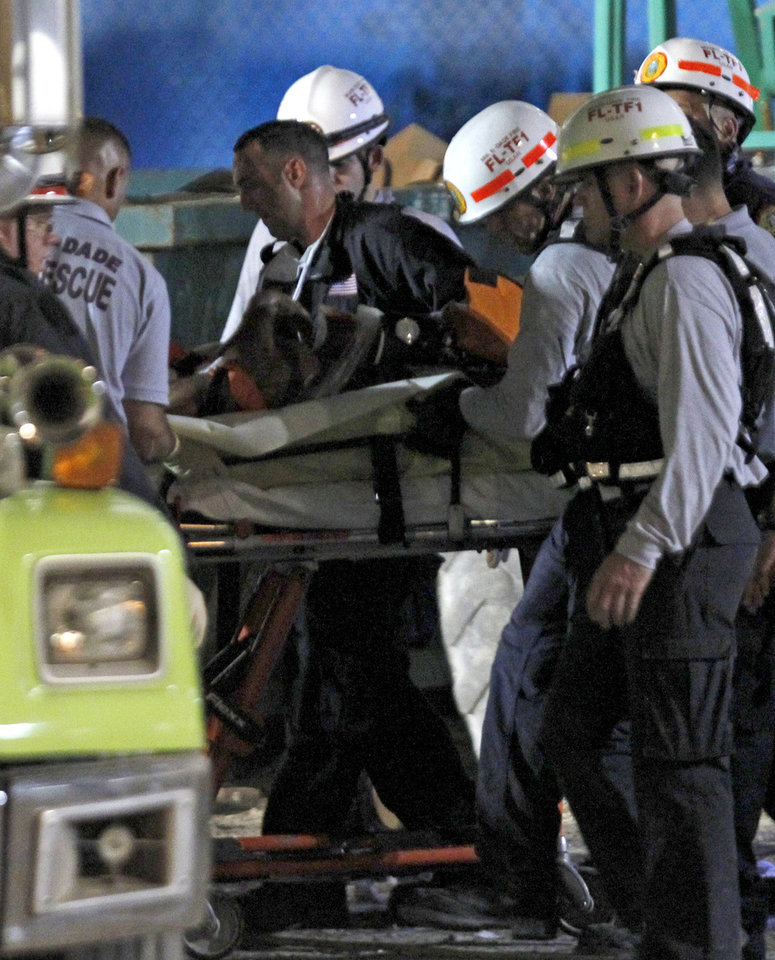 Photo -   Firefighters remove a victim from the rubble after a section of a parking garage under construction at Miami-Dade College campus collapsed, early morning Thursday, Oct. 11, 2012 in Doral, Fla. A section of a parking garage under construction at a community college collapsed on Wednesday, Oct. 10, killing one worker and trapping another in the rubble, officials said. At least 10 other workers were hurt when the roof of the five-story concrete garage fell, creating a pancake-style collapse on the campus of Miami-Dade College, officials said. (AP Photo/Alan Diaz)