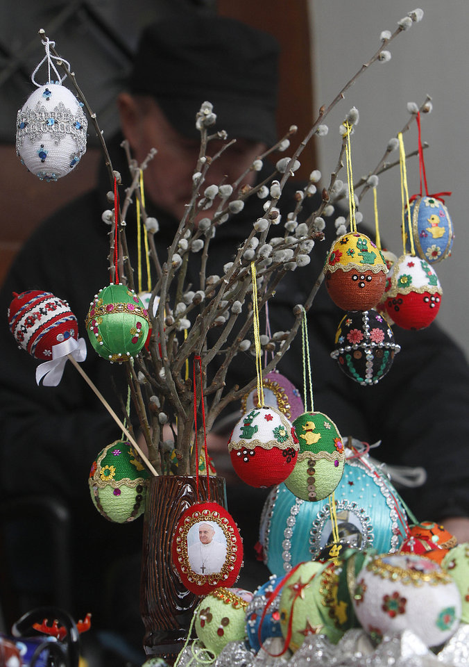 Photo - People look at handmade palms and Easter Eggs in Warsaw, Poland, Saturday, April 12, 2014, a day ahead of Palm Sunday, which opens the Holy Week that ends with Easter Sunday, the most important Catholic holiday. (AP Photo/Czarek Sokolowski)