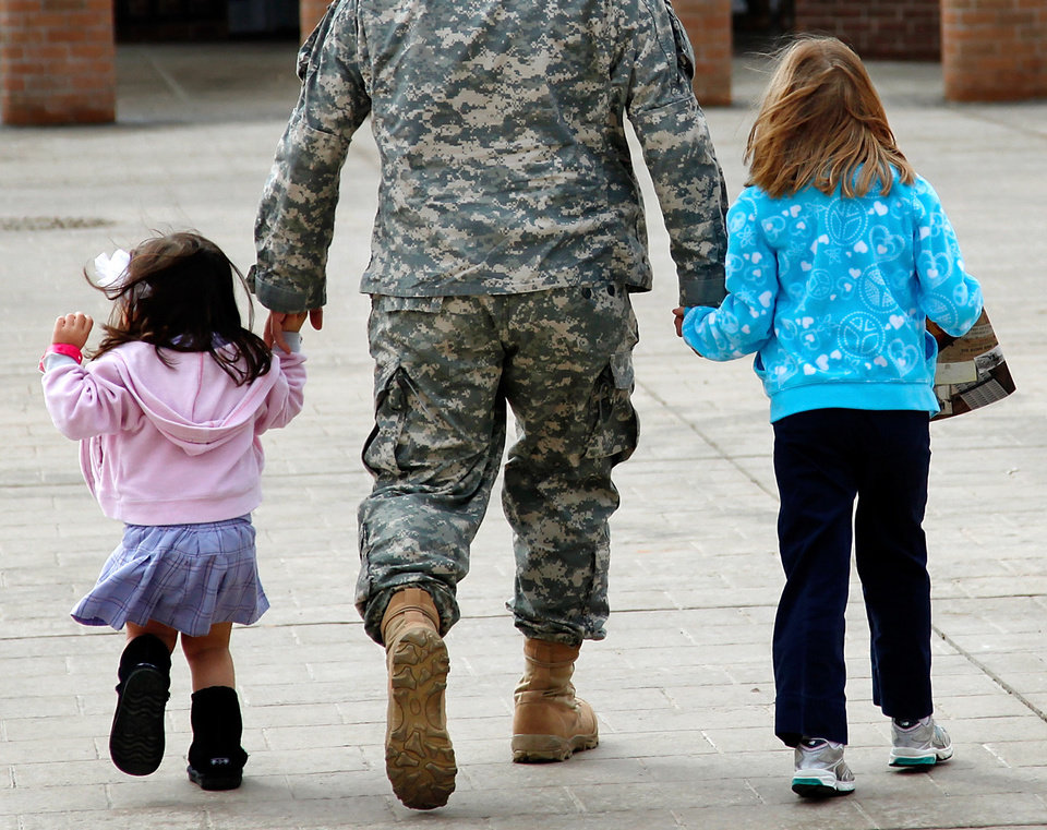 A soldier holds the hands of two small girls as he walks with them into the Oklahoma City Arena to attend the 45th Infantry Brigade Combat Team deployment ceremony inside the Cox Convention Center,  Wednesday, Feb. 16, 2011.  Photo by Jim Beckel, The Oklahoman