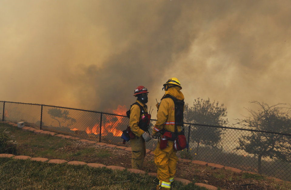 Photo - Two firefighters discuss a strategy change while fighting a wildfire from the backyard of a home Thursday, May 15, 2014, in San Marcos, Calif. Gusty winds failed to return Thursday in San Diego County wildfire areas and authorities said it was a window of opportunity to make further gains against flames that have charred thousands of acres and burned homes. (AP Photo)