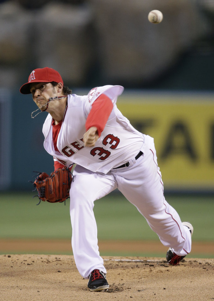Photo - Los Angeles Angels starting pitcher C.J. Wilson throws against the Seattle Mariners during the first inning of an MLB American League baseball game on Tuesday, April 1, 2014, in Anaheim, Calif. (AP Photo/Jae C. Hong)