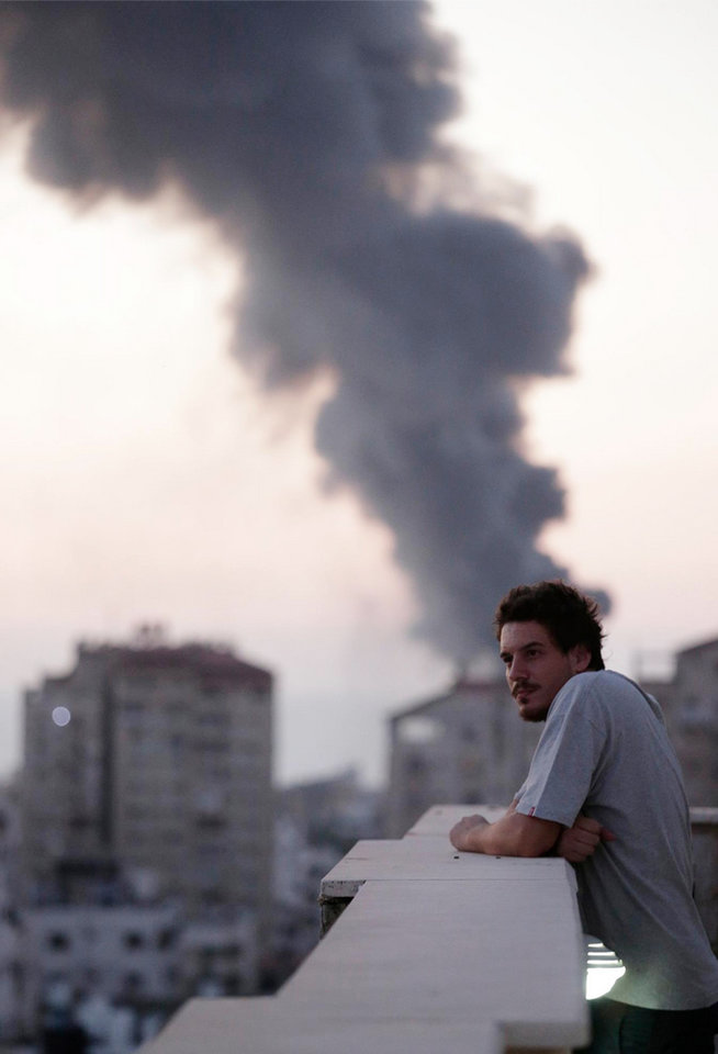 Photo - This photo taken in August, 2014 shows Associated Press video journalist Simone Camilli on a balcony overlooking smoke from Israeli Strikes in Gaza City. Camilli, 35, was killed in an ordnance explosion in the Gaza Strip, on Wednesday, Aug. 13, 2014 together with Palestinian translator Ali Shehda Abu Afash and three members of the Gaza police. Police said four other people were seriously injured, including AP photographer Hatem Moussa.(AP Photo/Lefteris Pitarakis)