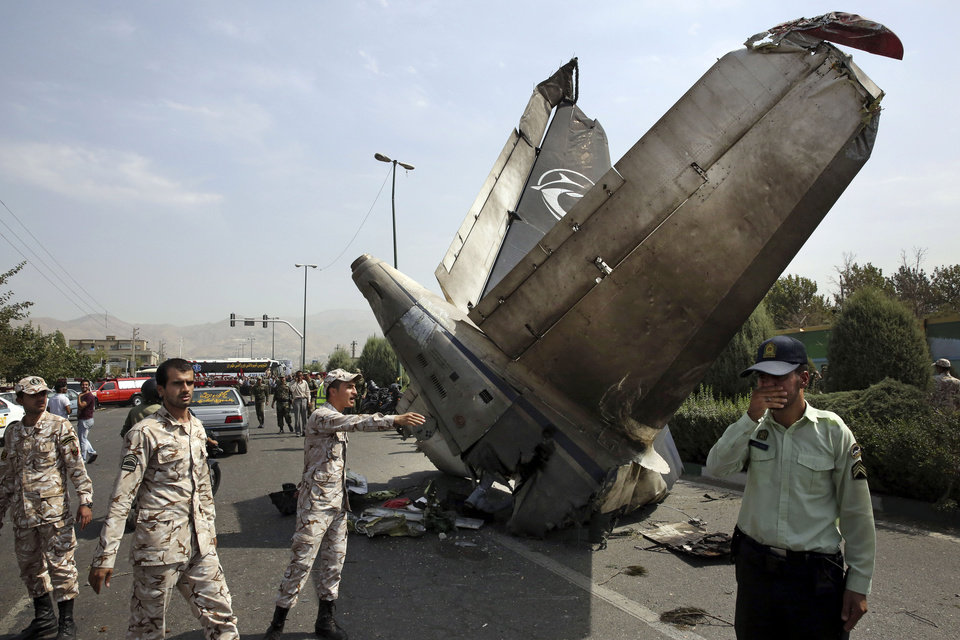 Photo - Iranian Revolutionary Guards and police officers inspect the site of a passenger plane crash near the capital Tehran, Iran, Sunday, Aug. 10, 2014. An Iranian passenger plane crashed Sunday while taking off from an airport near the capital, killing tens of people onboard, state media reported. (AP Photo/Vahid Salemi)