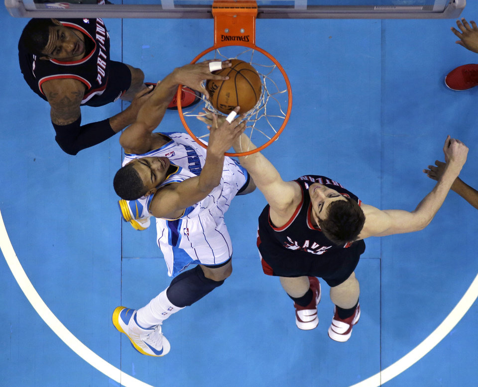 Photo - New Orleans Hornets forward Anthony Davis (23) dunks between Portland Trail Blazers forwards Victor Claver, right, and LaMarcus Aldridge during the first half of an NBA basketball game in New Orleans, Wednesday, Feb. 13, 2013. (AP Photo/Gerald Herbert)