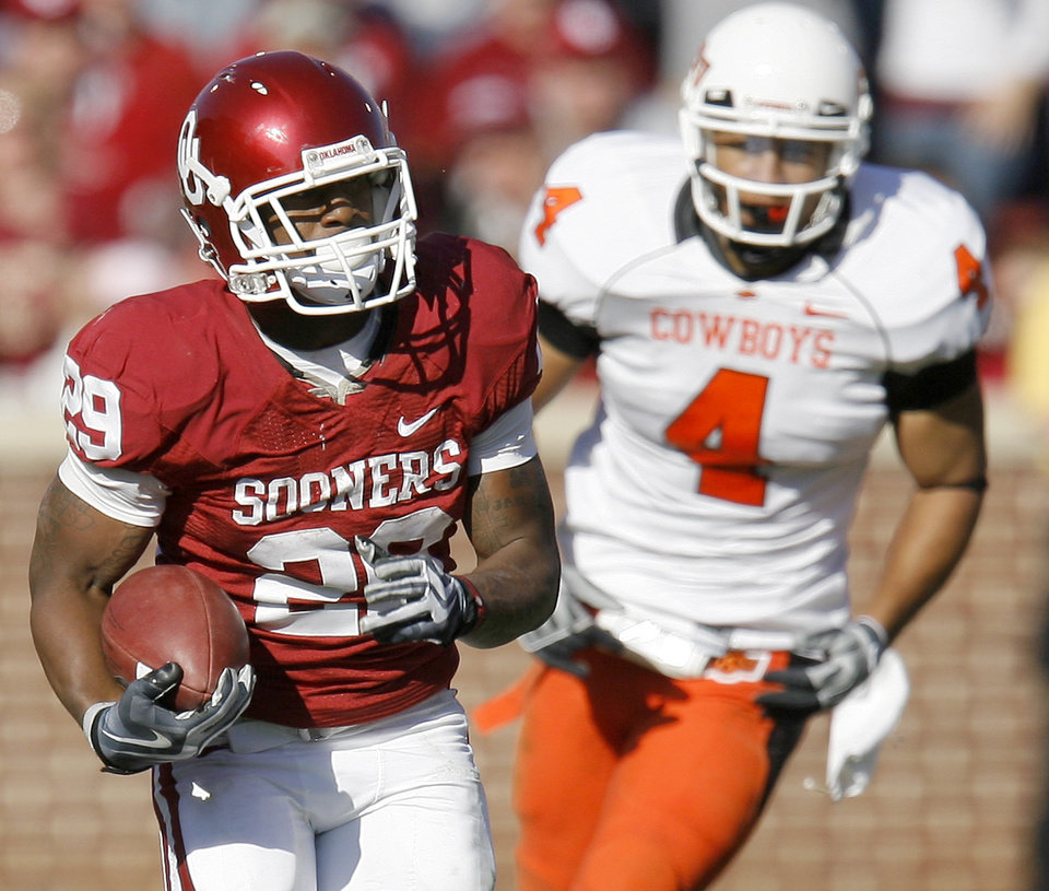 Photo - OU's Chris Brown runs the ball past OSU's Patrick Lavine during the second half of the Bedlam college football game between the University of Oklahoma Sooners (OU) and the Oklahoma State University Cowboys (OSU) at the Gaylord Family-Oklahoma Memorial Stadium on Saturday, Nov. 28, 2009, in Norman, Okla.
