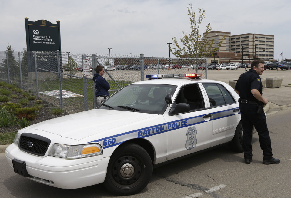 Photo - A police officer blocks the entrance to a Veterans Affairs hospital after the building seen at right rear was locked down after a shooting, Monday, May 5, 2014, in Dayton, Ohio. A city official says a suspect is in police custody after the shooting that left one person with a minor injury. (AP Photo/Al Behrman)