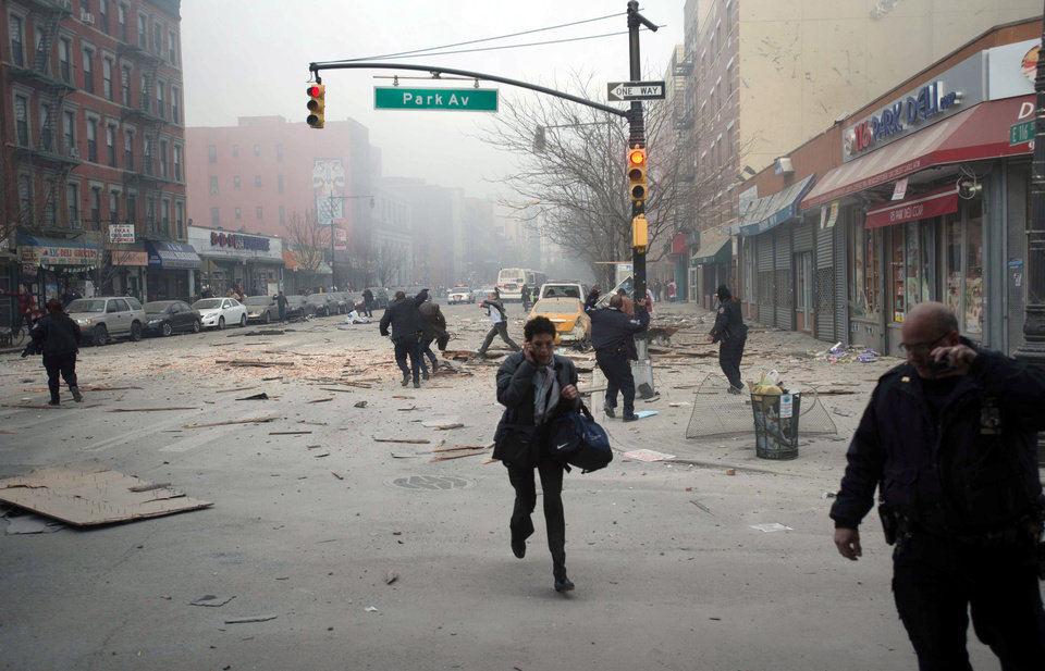 Photo - People run after an explosion and building collapse in the East Harlem neighborhood of New York, Wednesday, March 12, 2014. The explosion leveled an apartment building, and sent flames and billowing black smoke above the skyline. (AP Photo/Jeremy Sailing)