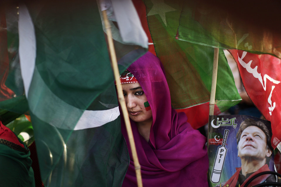 Photo - A Pakistani supporter of former cricket star-turned-politician, and leader of Pakistan Tehreek-e-Insaf party, Imran Khan, takes part during a rally in Khan's support in Islamabad, Pakistan, Thursday, May 9, 2013. Pakistan is scheduled to hold parliamentary elections on May 11, the first transition between democratically elected governments in a country that has experienced three military coups and constant political instability since its creation in 1947. The parliament's ability to complete its five-year term has been hailed as a significant achievement. Headband reads,