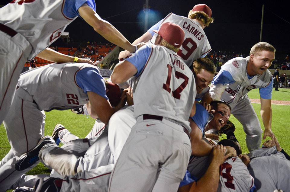 Oklahoma's Ethan Carnes (19), Kindle Ladd (17), and Kyle Hayes (36) celebrate with teammates after an NCAA college baseball tournament regional game against Virginia Tech at English Field in Blacksburg, Va., Sunday, June 2, 2013. (AP Photo/Michael Shroyer) ORG XMIT: VAMS166