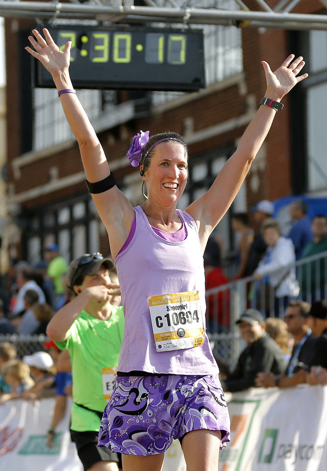 Photo - Anna Johnson raises her arms in celebration after finishing the half marathon during the Oklahoma Memorial Marathon in Oklahoma City, Okla. on Sunday, April 24, 2016.   Photo by Chris Landsberger, The Oklahoman