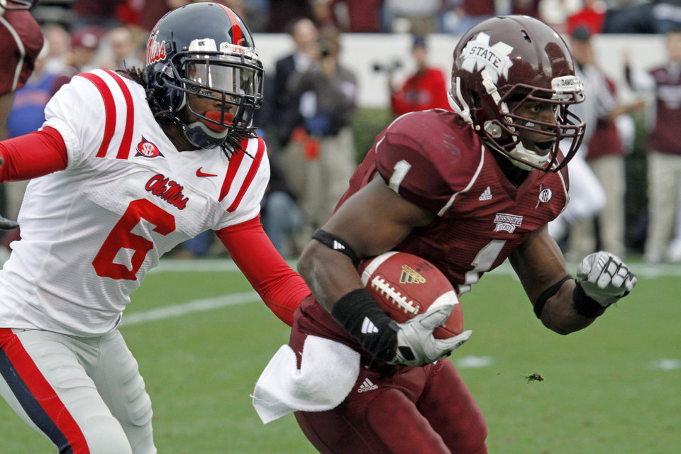 Photo - Mississippi cornerback Jeremy McGee (6) tries to tackle Mississippi State wide receiver Chad Bumpus (1) as he runs to the end zone for a third-quarter 34-yard touchdown during their NCAA college football game in Starkville, Miss., Saturday, Nov. 28, 2009. Mississippi State defeated No. 20 Mississippi, 41-27. (AP Photo/Rogelio V. Solis) ORG XMIT: MSRS112