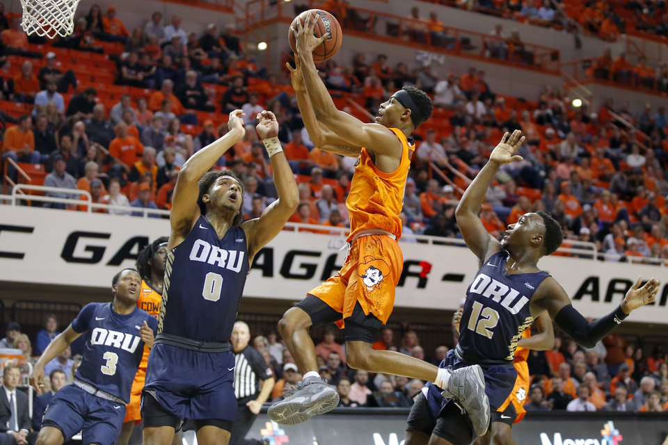 Photo - Oklahoma State's Avery Anderson (0) goes to the basket as Oral Roberts' Kevin Obanor (0) and R.J. Fuqua (12) defend during an NCAA basketball game between the Oklahoma State University Cowboys (OSU) and the Oral Roberts Golden Eagles (ORU) at Gallagher-Iba Arena in Stillwater, Okla., Wednesday, Nov. 6, 2019. [Bryan Terry/The Oklahoman]