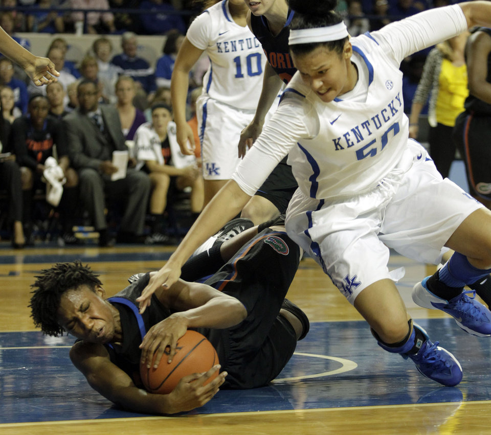 Photo - Florida's Kayla Lewis, left, pulls in a loose ball next to Kentucky's Azia Bishop during the first half of an NCAA college basketball game on Sunday, Jan. 5, 2014, in Lexington, Ky. (AP Photo/James Crisp)
