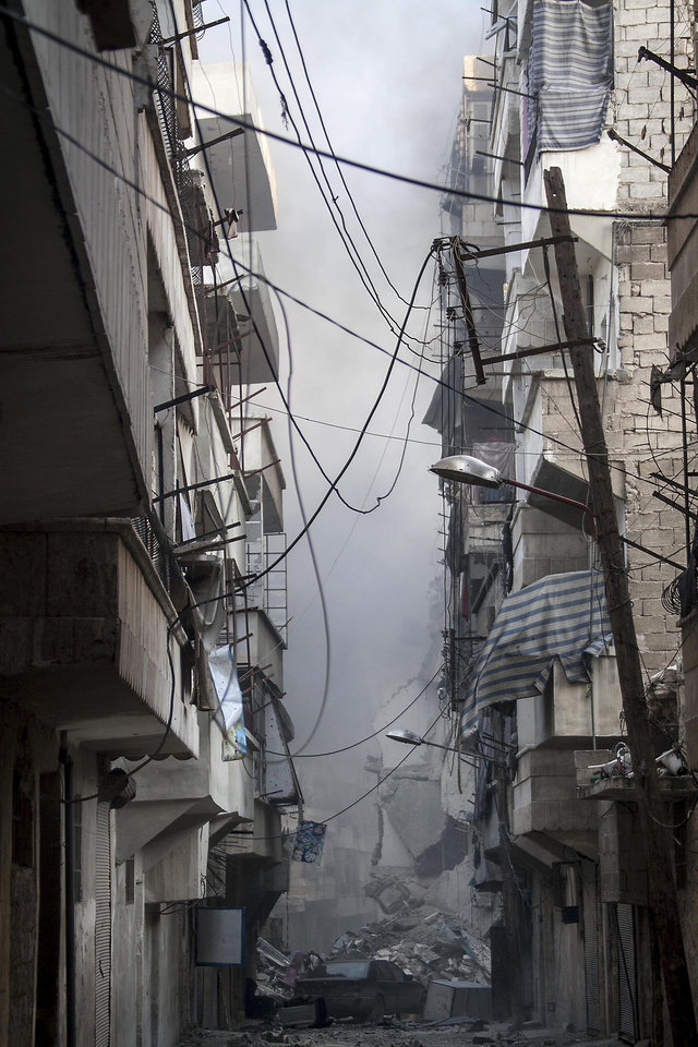 Photo - In this Wednesday, Dec. 5, 2012 photo, smoke rises from residential buildings due heavy fighting between Free Syrian Army fighters and government forces in Aleppo, Syria. (AP Photo/Narciso Contreras)