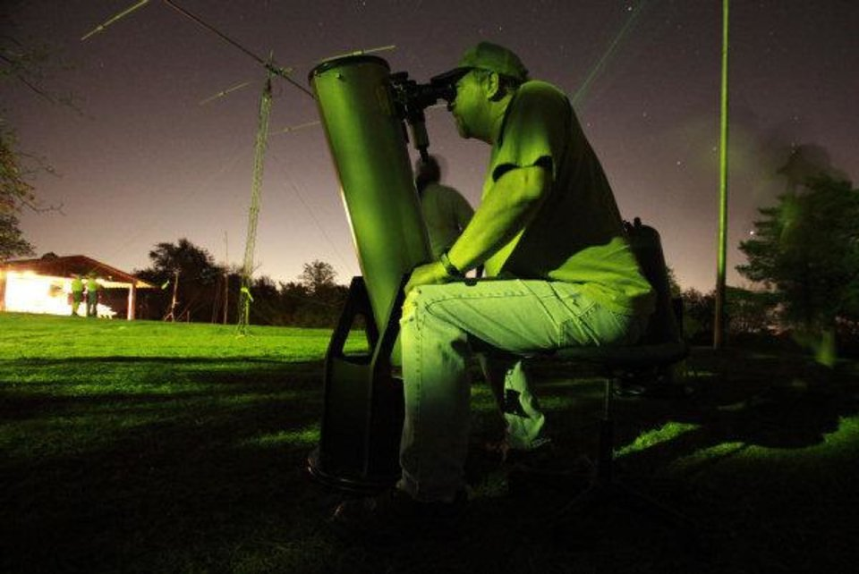 Photo - Bill Wilburn, with the Oklahoma City Astronomy Club, looks at the Hercules star cluster with his 8-inch telescope during the 54th Jamboree-On-The -Air at John Nichols Scout Ranch last weekend.  David McDaniel - THE OKLAHOMAN