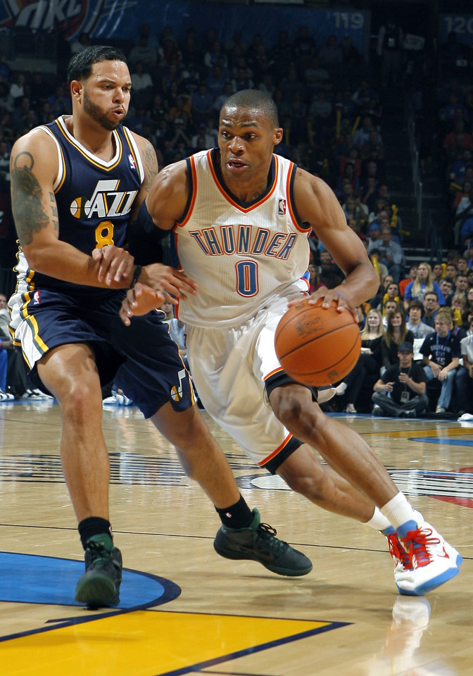 Photo - Oklahoma City's Russell Westbrook tries to get by Utah's Deron Williams during the NBA basketball game between the Oklahoma City Thunder and Utah Jazz in the Oklahoma City Arena on Sunday, Oct. 31, 2010. Photo by Sarah Phipps, The Oklahoman