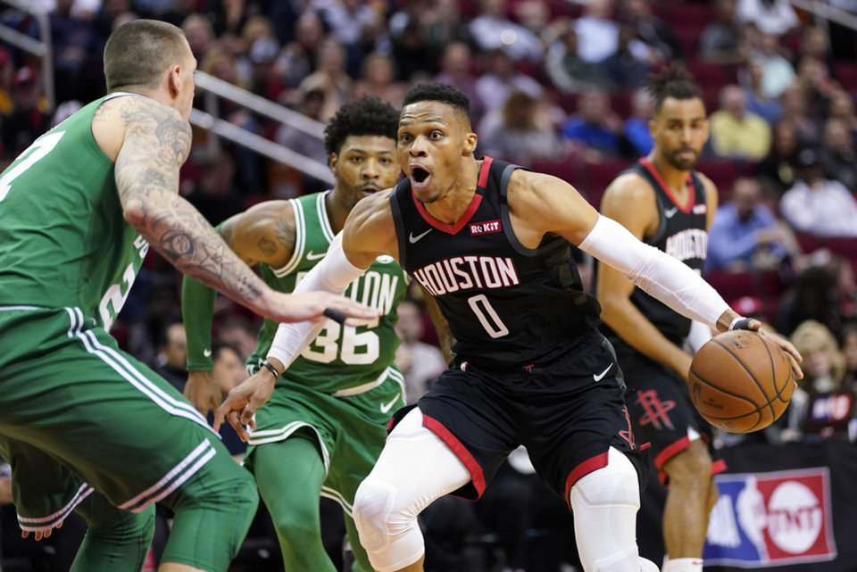 Photo - Houston Rockets' Russell Westbrook (0) drives toward the basket as Boston Celtics' Daniel Theis, left, defends during the first half of an NBA basketball game Tuesday, Feb. 11, 2020, in Houston. (AP Photo/David J. Phillip)