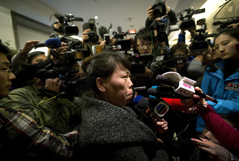 Photo - A Chinese relative of passengers aboard a missing Malaysia Airlines plane is surrounded by media as she answers questions about how families are being compensated outside a hotel room set aside for relatives or friends of passengers aboard the missing airplane in Beijing, China Tuesday, March 11, 2014.  Authorities hunting for the missing Malaysia Airlines jetliner expanded their search on land and sea Tuesday, reflecting the difficulties in finding traces of the Boeing 777 more than three days after it vanished with 239 people on board.   (AP Photo/Andy Wong)